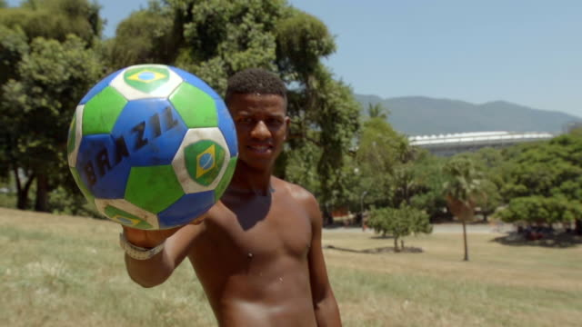 Teenager holds Brazilian flag soccer ball up to camera on hillside overlooking World Cup stadium