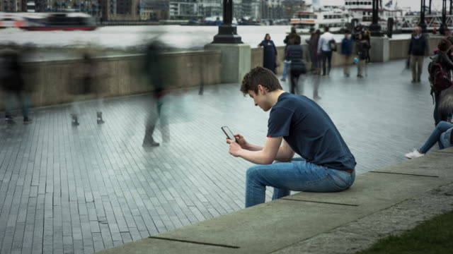 a teenager is absorbed with his mobile phone oblivious of the rapidly moving street life around him - remote location phone stock videos & royalty-free footage