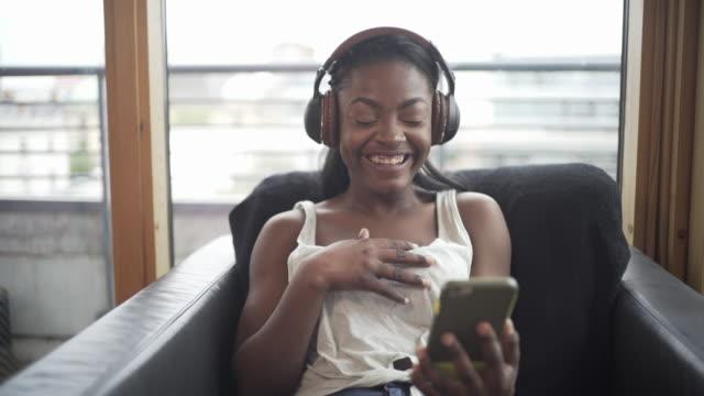 vídeos de stock, filmes e b-roll de a teenager listening to a podcast - mãos cobrindo boca