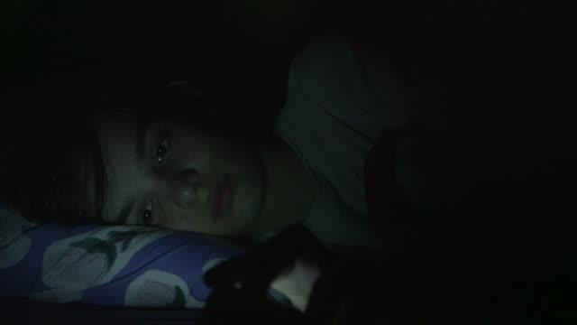 teenager looks at the screen of a phone in bed at night - abhängigkeit stock-videos und b-roll-filmmaterial