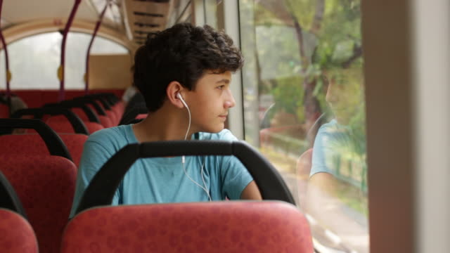 ms teenager on a bus looking out of window - mp3プレイヤー点の映像素材/bロール