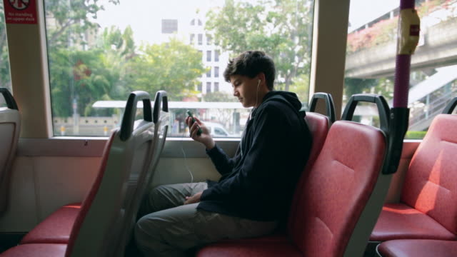 vídeos de stock, filmes e b-roll de ws teenager on a bus using smartphone listening to music - bus
