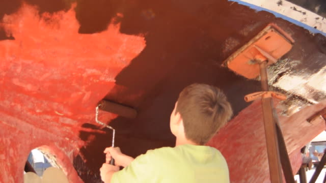 teenager painting the hull of a sailboat - dry dock stock videos & royalty-free footage