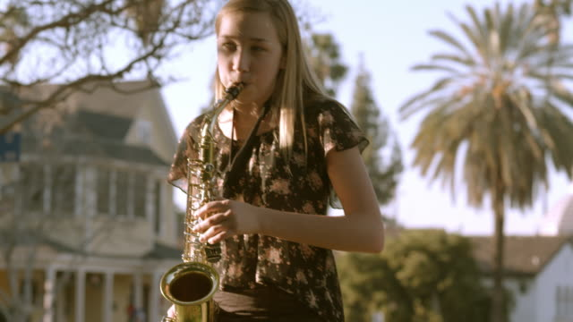 teenager playing brass saxophone practices her instrument in backyard of her home / redlands, california, usa - saxophone stock videos and b-roll footage