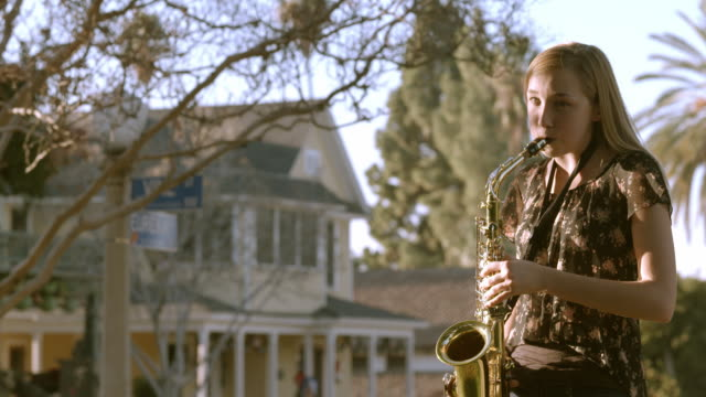 teenager playing brass saxophone practices her instrument in backyard of her home / redlands, california, usa - one teenage girl only stock videos & royalty-free footage