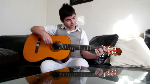 vídeos y material grabado en eventos de stock de adolescente tocando la guitarra - diapasón instrumento de cuerdas
