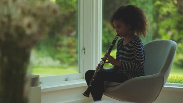teenager plays the clarinet in front of a window in her house - clarinet stock videos & royalty-free footage