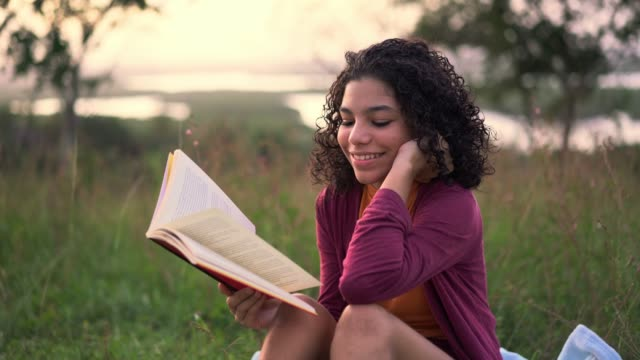 teenager reading a book sitting on the grass - summer reading stock videos & royalty-free footage