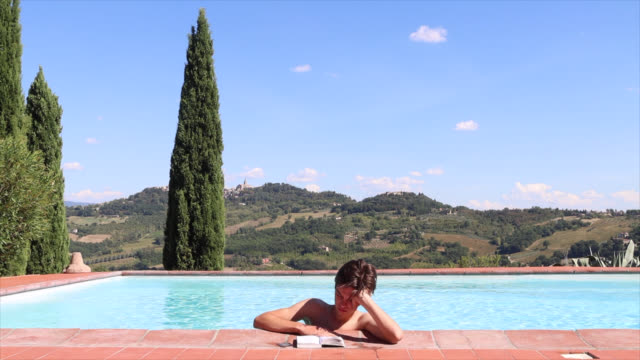 teenager reads a book in the swimming pool - endast en tonårspojke bildbanksvideor och videomaterial från bakom kulisserna