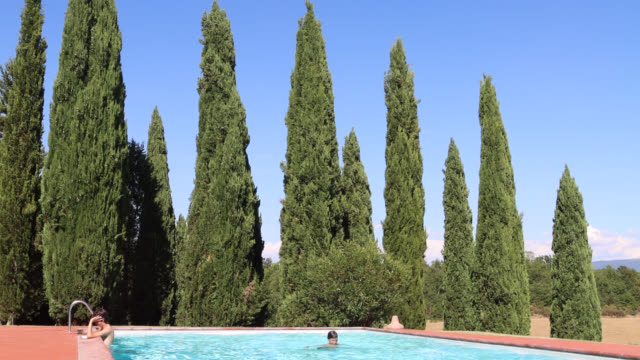 teenager reads a book in the swimming pool - schwimmbeckenrand stock-videos und b-roll-filmmaterial