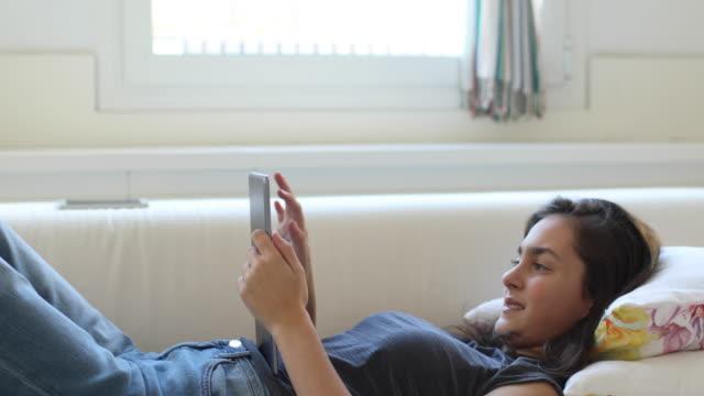 Teenager, relaxen und liegen in einem Sofa mit digital-Tablette.