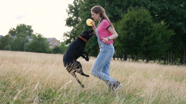 Teenager running with ball followed by excited dog.