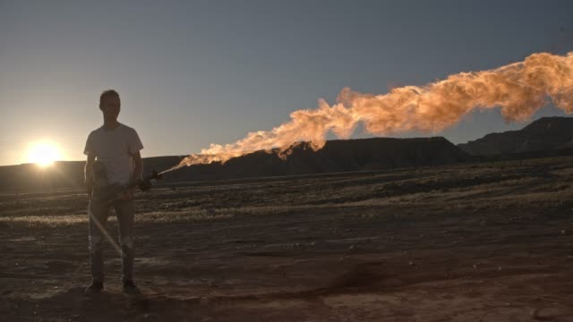 vídeos de stock e filmes b-roll de teenager shoots a flamethrower - arremessar