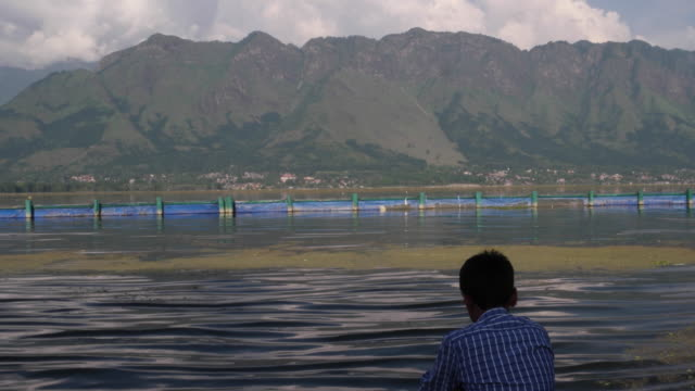 stockvideo's en b-roll-footage met a teenager sitting at the steps of dal lake banks, with himalayas in the backdrop,  at the hazratbal mosque in srinagar, - alleen één tienerjongen