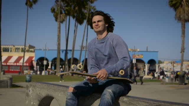 teenager sitting on rail playing with his skateboard looking ahead venice california skatepark - un ragazzo adolescente video stock e b–roll