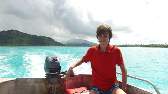teenager steering boat on water - huahine island stock videos and b-roll footage