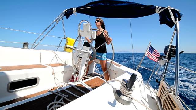 hd: teenager steering the sailboat - kapten bildbanksvideor och videomaterial från bakom kulisserna