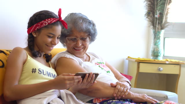 teenager mit ihrem handy mit ihrer großmutter - teenager alter stock-videos und b-roll-filmmaterial
