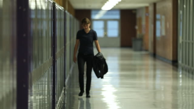 stockvideo's en b-roll-footage met teenager walking alone in empty school hallway - lockerkast