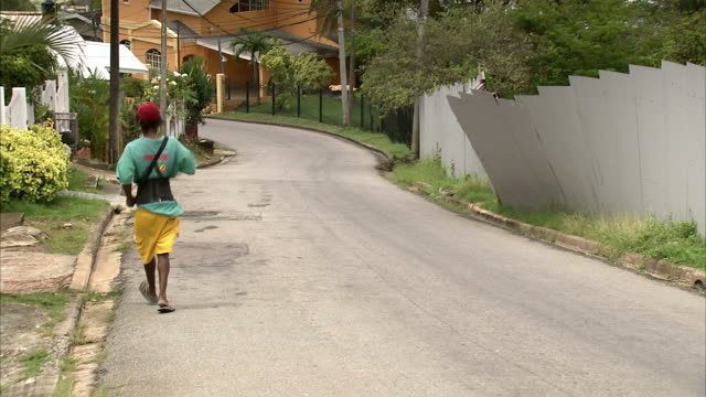 a teenager walks down a hillside street. available in hd. - trinidad trinidad and tobago stock videos & royalty-free footage