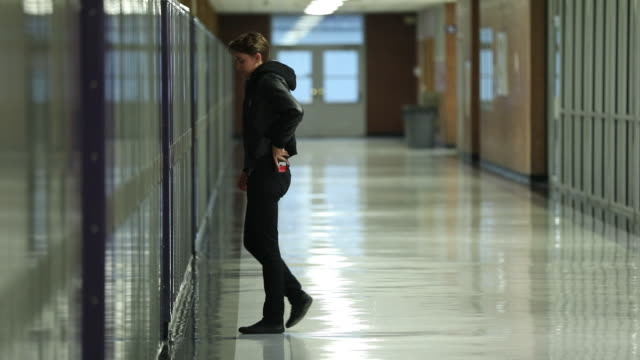 stockvideo's en b-roll-footage met teenager walks over to lockers and sits on the ground - lockerkast