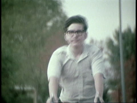 1973 montage teenager wearing glasses riding bike on suburban street, vo talking about math / united states - geek stock videos & royalty-free footage