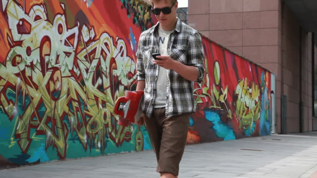 PAN of teenager with board texting past graffitti wall
