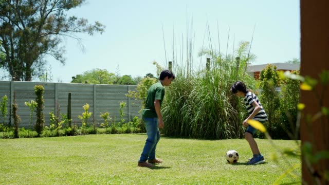 teenagers are playing soccer in a yard - domestic garden stock videos & royalty-free footage