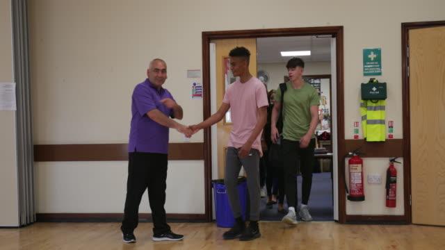vidéos et rushes de adolescents qui arrivent au club pour les jeunes - centre culturel