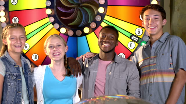 vídeos de stock e filmes b-roll de teenagers at amusement arcade by wheel of fortune - 12 13 years