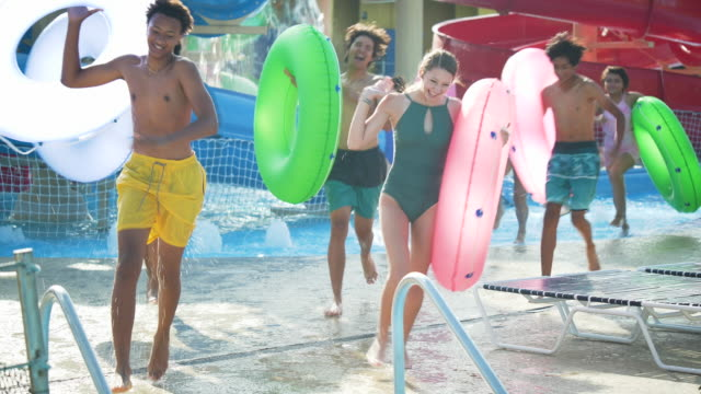 vídeos de stock, filmes e b-roll de adolescentes em parque aquático entrando em rio preguiçoso - teenagers only
