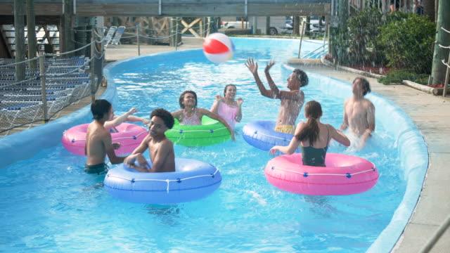 jugendliche im wasserpark in faulen fluss mit strandball - multi ethnic group stock-videos und b-roll-filmmaterial