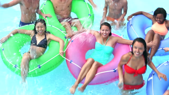 Teenagers at water park playing on lazy river
