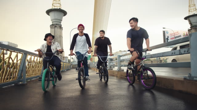 vídeos de stock, filmes e b-roll de adolescentes ciclistas de bmx pedalando na cidade de bangkok. - amizade masculina