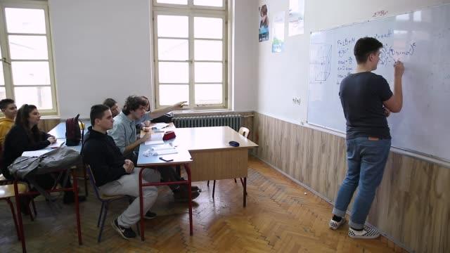 ティーンエイジャーは、ホワイトボードの前で同級生にいじめや紙のボールを投げる - 教室点の映像素材/bロール