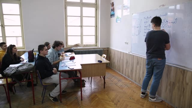 teenagers bullying and throwing paper balls at classmate in front of whiteboard - birichinata video stock e b–roll