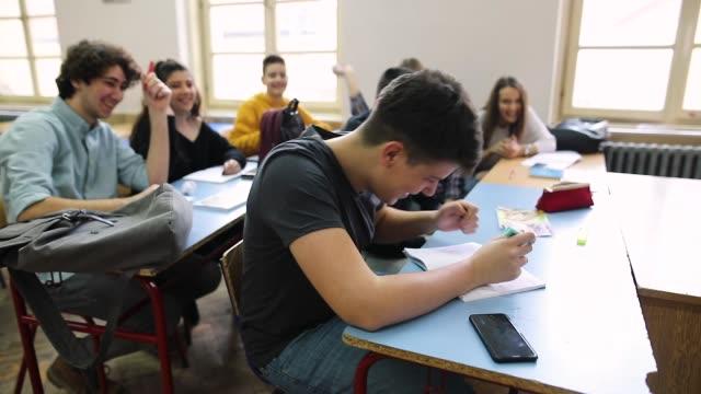 teenagers bullying and throwing paper balls at classmate - birichinata video stock e b–roll