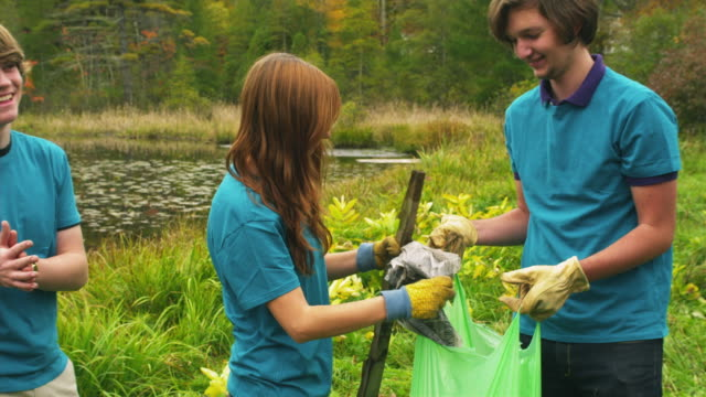 ms shaky teenagers cleaning lake shore from garbage, dorset, vermont, usa - wackelaufnahme stock-videos und b-roll-filmmaterial