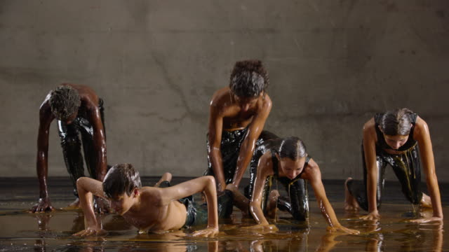 Teenagers dance around covered in honey, slow motion
