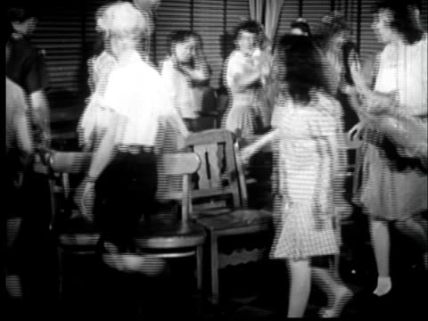 vídeos de stock e filmes b-roll de 1945 ms teenagers dressed as children playing musical chairs at party/ sylacauga, alabama - sentar se