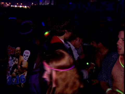 Teenagers dressed up and dancing at a rave