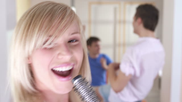 stockvideo's en b-roll-footage met hd: teenagers having fun imitating music band - haarborstel