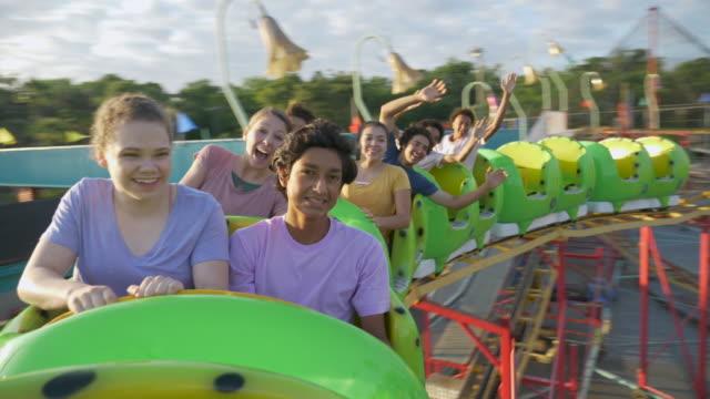 jugendliche, die spaß am achterbahnfahren haben - multi ethnic group stock-videos und b-roll-filmmaterial