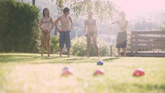 SELECTIVE FOCUS Teenagers in bathing suits playing bocce / Stowe, Vermont, United States