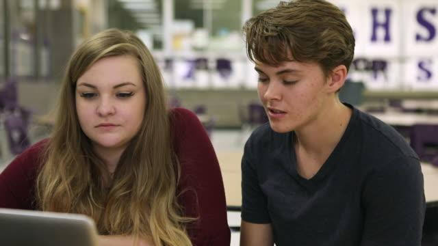 teenagers in classroom looking at laptop - リーハイ点の映像素材/bロール