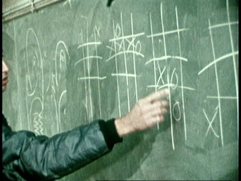 vídeos de stock, filmes e b-roll de 1973 montage teenagers in classroom playing tic tac toe on blackboard / united states - 1973