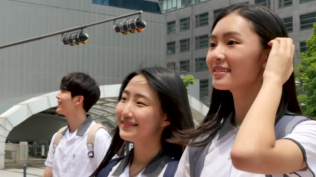 teenagers in school uniform crossing street at the crosswalk - female high school student stock videos & royalty-free footage