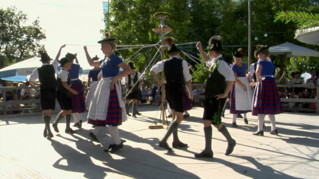 WS Teenagers in traditional clothing dancing around maypole at Tegernsee folk festival, Tegernsee, Bavaria, Germany