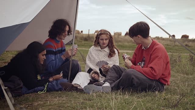 teenagers joking around playing a game of cards on a camping trip - east sussex stock videos & royalty-free footage