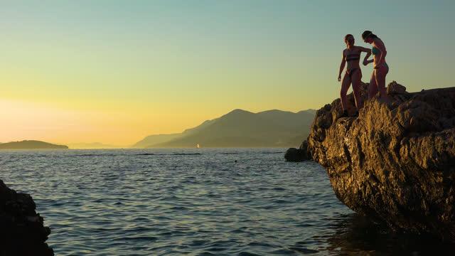 vídeos y material grabado en eventos de stock de adolescentes saltando de un clif al atardecer en la costa de croacia y nadando de vuelta a la costa, cerca de dubrovnik - amistad femenina